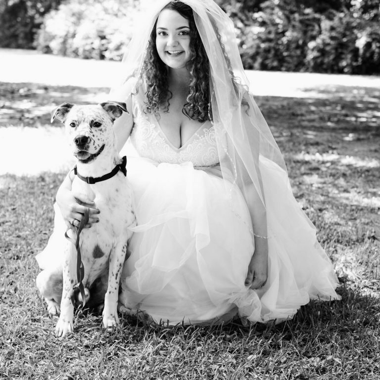 Black and white image of Savanna wearing a wedding dress and crouching down with her dog. She is smiling.